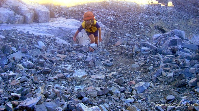 Chris grunting up a steep rocky slope