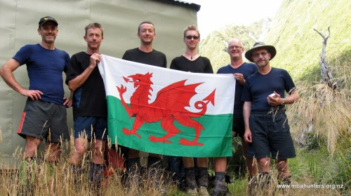 A traditional photo between a Welsh flag and the Neave hut...